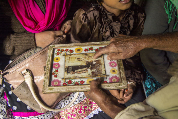 old tribal lady showing her momorable photo to guests Guests Here Belongs To Me History Holding Lifestyles Memories Old Lady Photo In A Frame Portrait Showing Photo Sitting Wrinkled Hand