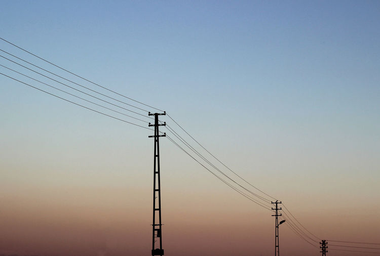 Low angle view of silhouette electricity pylon against gradient sky