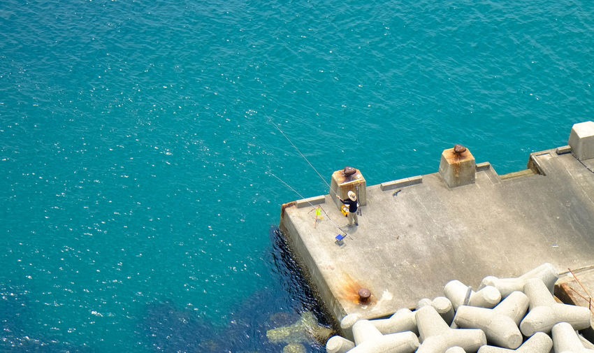 High angle view of man fishing on pier