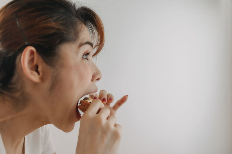 Close-up portrait of a young woman holding ice cream