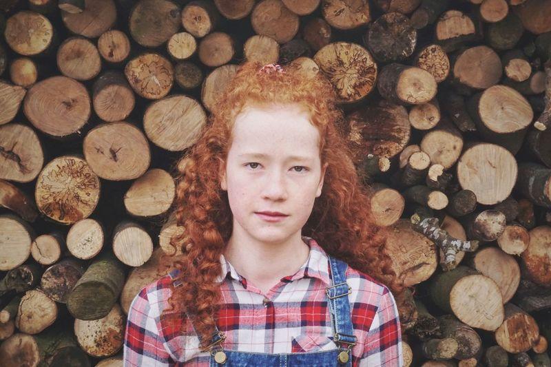 Portrait of boy standing on logs
