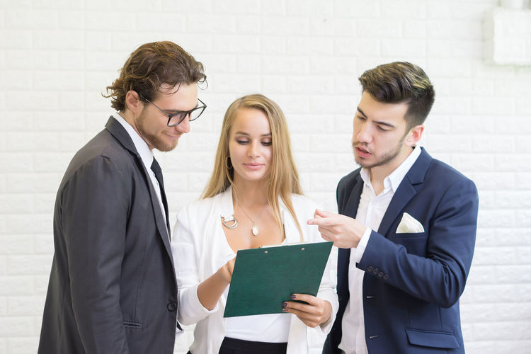 Business colleagues discussing over document while standing in office