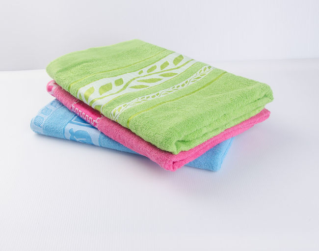 High angle view of colorful towels stacked on table against white background