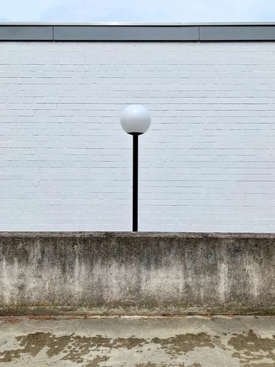 Low angle view of street light against wall