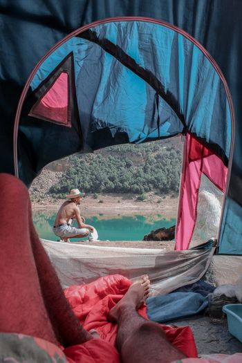 Low section of man in tent against lake