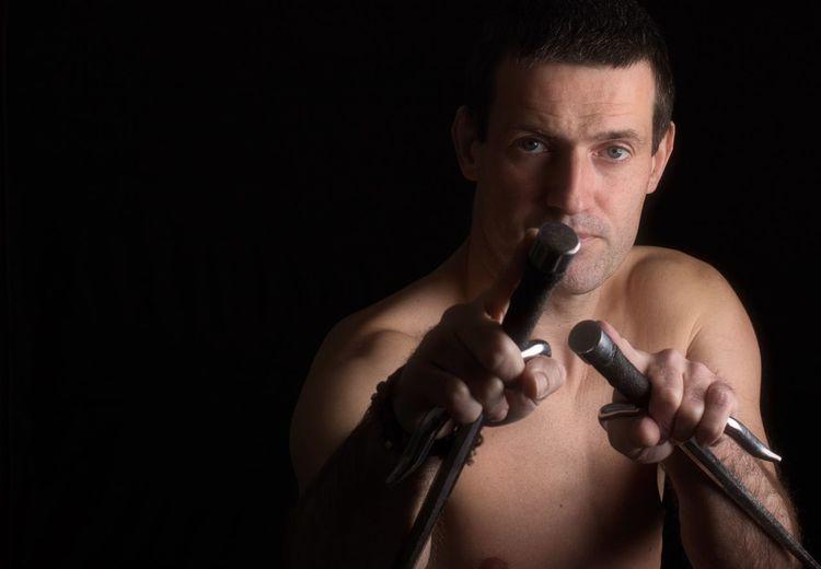 Portrait of shirtless man holding swords against black background