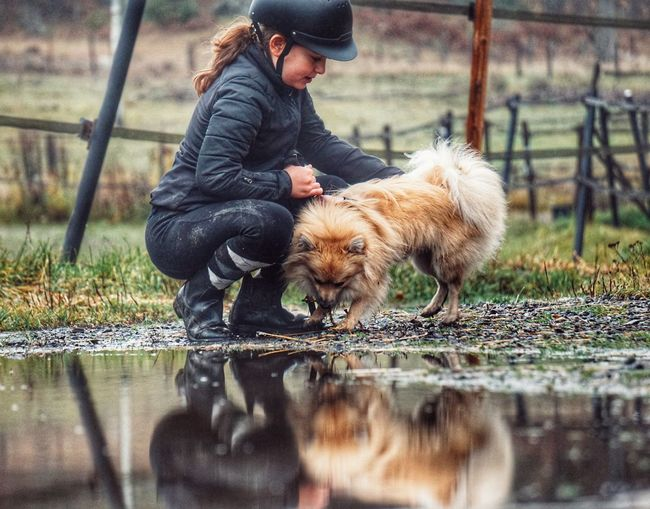 Cute girl holding dog by water on land