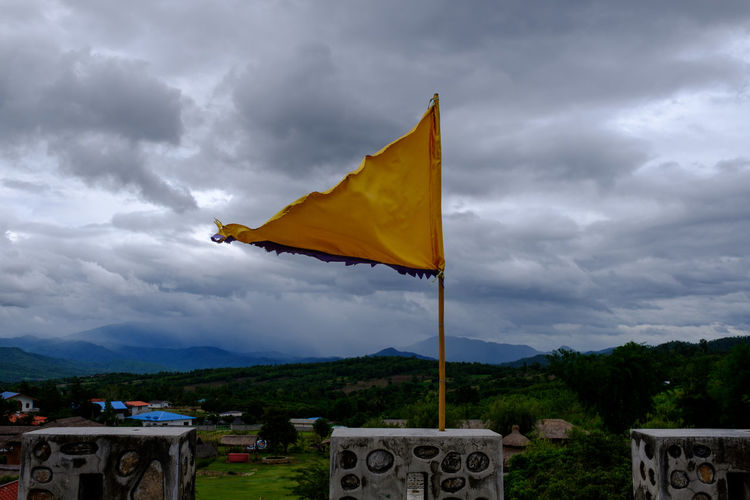 Yellow flag on built structure against cloudy sky