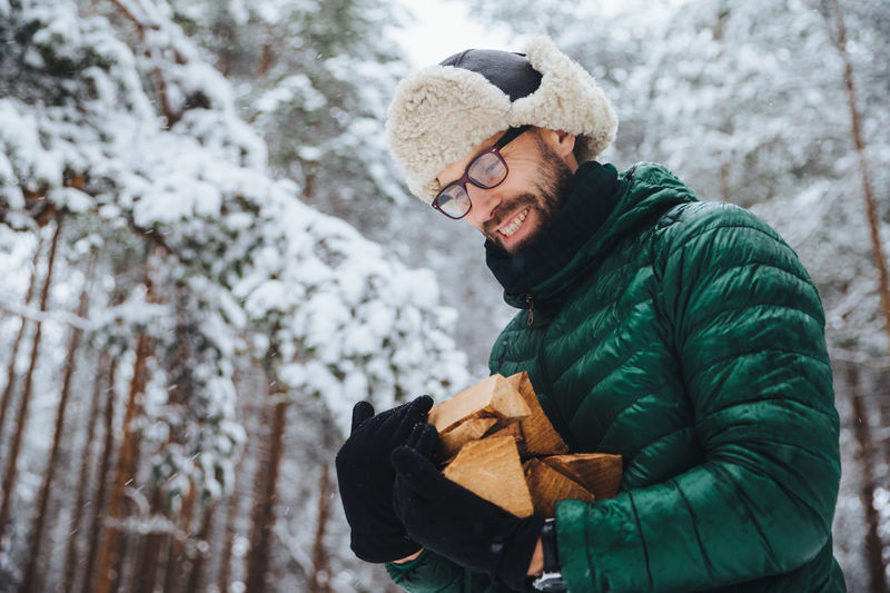 Man holding ice cream standing against trees during winter