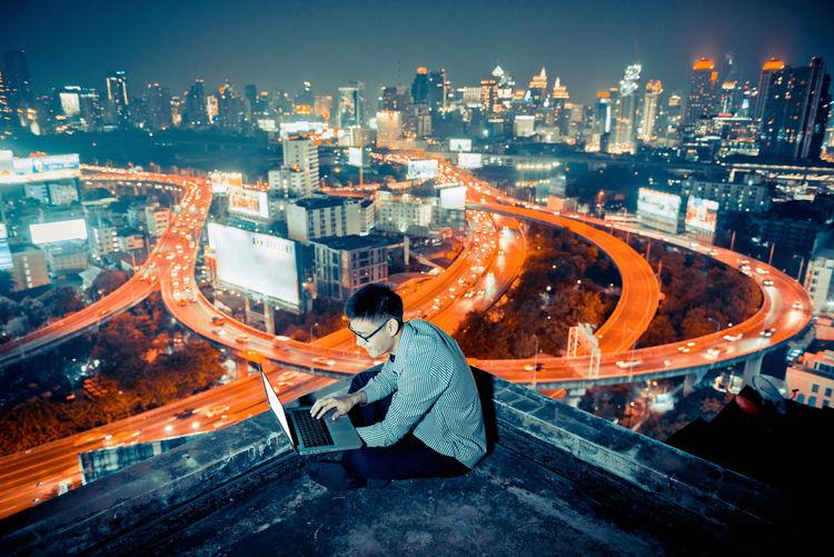Man sitting at illuminated cityscape against sky at night