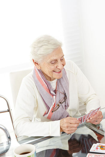 Senior woman playing cards at hospital