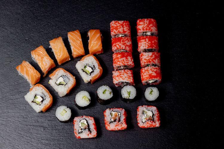 Directly above shot of sushi served on black background