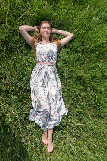 Directly Above Shot Of Young Woman Lying On Grassy Field