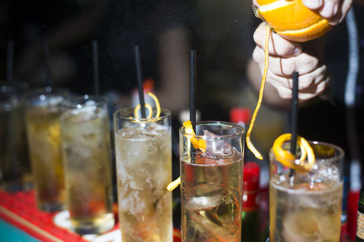 Cropped image of person garnishing cocktail glasses in bar
