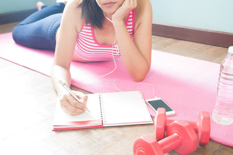 Low Section Of Woman Writing In Book While Listening Music On Mat At Home