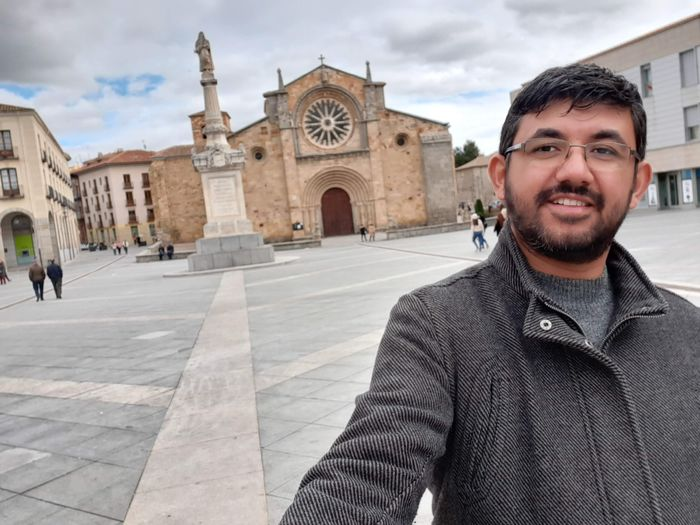 Portrait of smiling young man against church in city