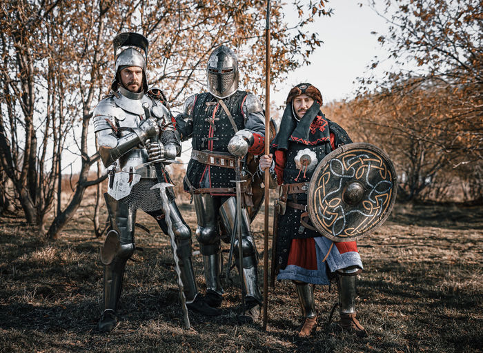 Portrait of warriors standing against trees