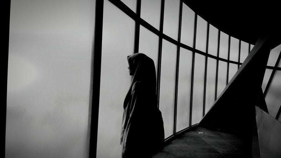 Side view of woman standing by window