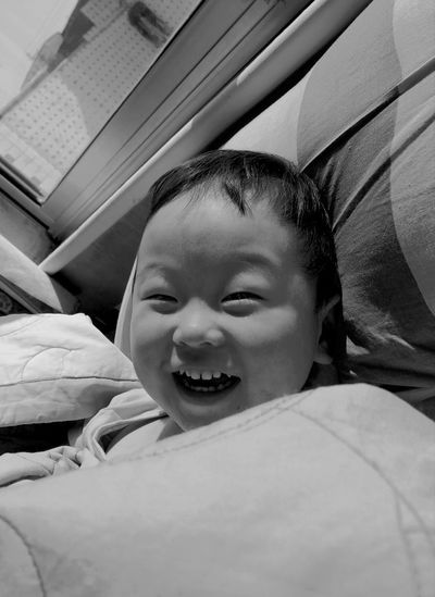 Portrait Of Smiling Boy Lying On Bed At Home