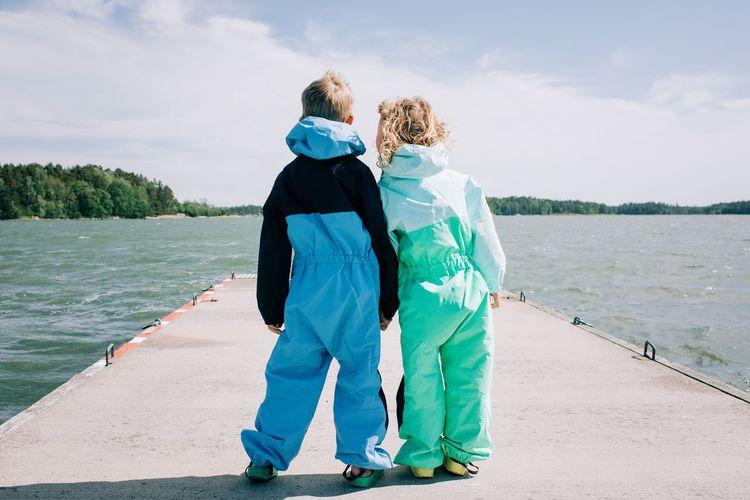 Rear view of friends walking by sea against sky