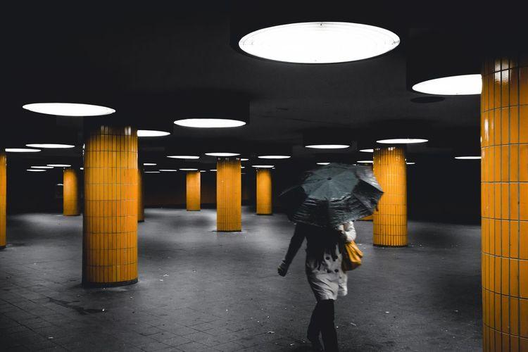Woman walking under umbrella at illuminated garage