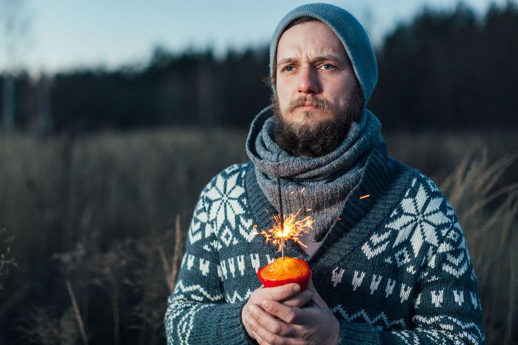 Close-up of man holding lit sparkler against blurred background
