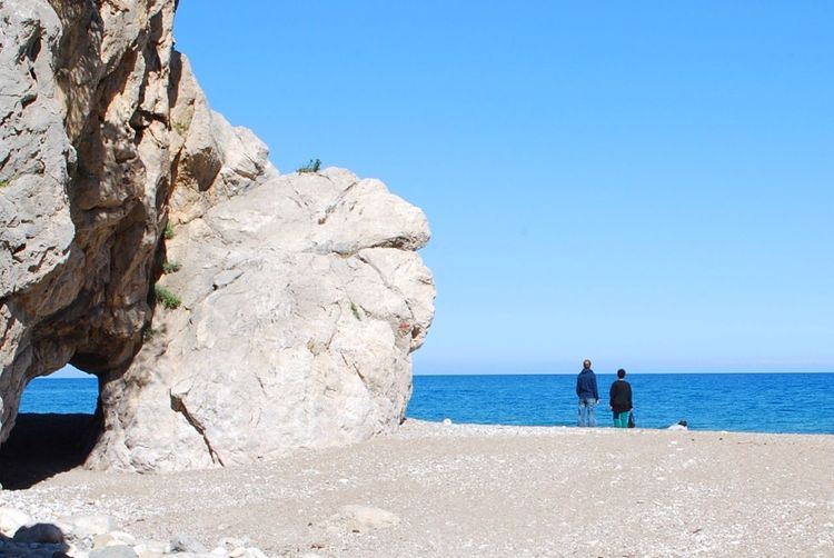 REAR VIEW OF TWO PEOPLE  CONTEMPLATING THE SEA