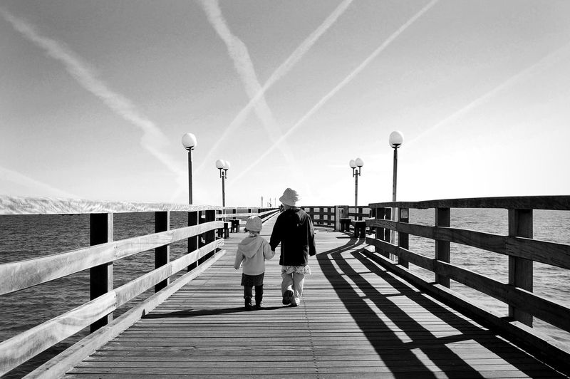 Rear view full length of girl walking with sister amidst sea on pier