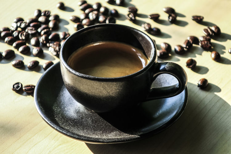 Close-Up Of Black Coffee With Beans On Table
