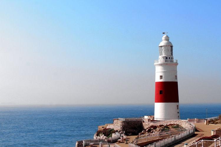Lighthouse against calm blue sea