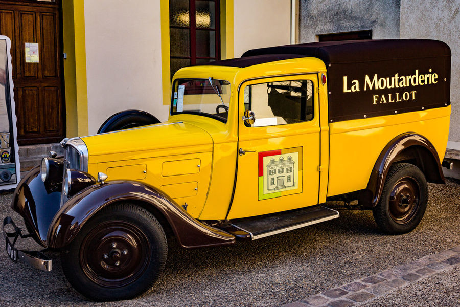 Building Exterior Built Structure Car City Day Land Vehicle Mode Of Transportation Motor Vehicle Mustard No People Outdoors Parking Retro Styled Road Stationary Street Transportation Travel Vintage Car Yellow