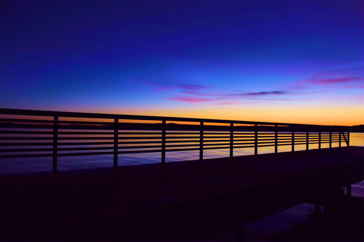 Silhouette Fence By Lake Against Sky During Sunset