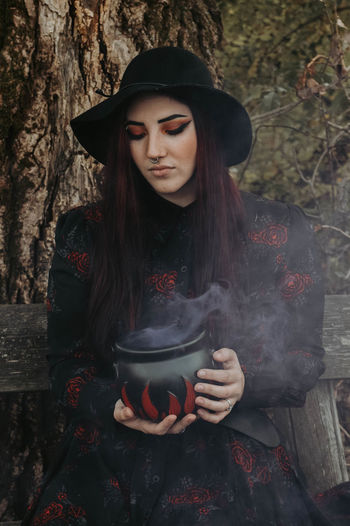 Young woman wearing hat while standing against plants