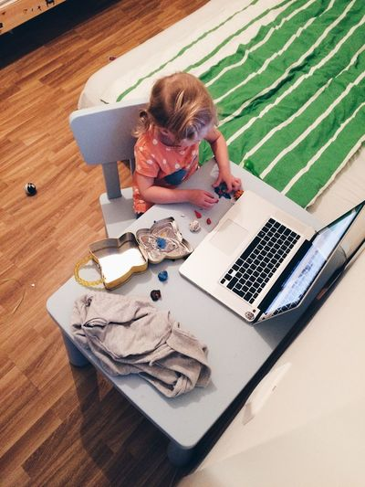 High Angle View Of Girl Playing With Clay By Laptop On Table At Home