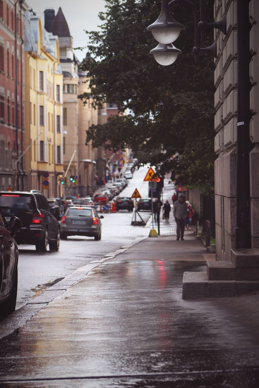 city, architecture, building exterior, built structure, transportation, car, street, motor vehicle, mode of transportation, wet, group of people, city life, rain, real people, crowd, road, land vehicle, people, nature