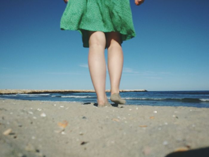Low section of woman on beach against clear sky
