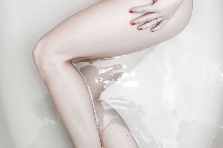 Midsection of sensuous woman lying in bathtub