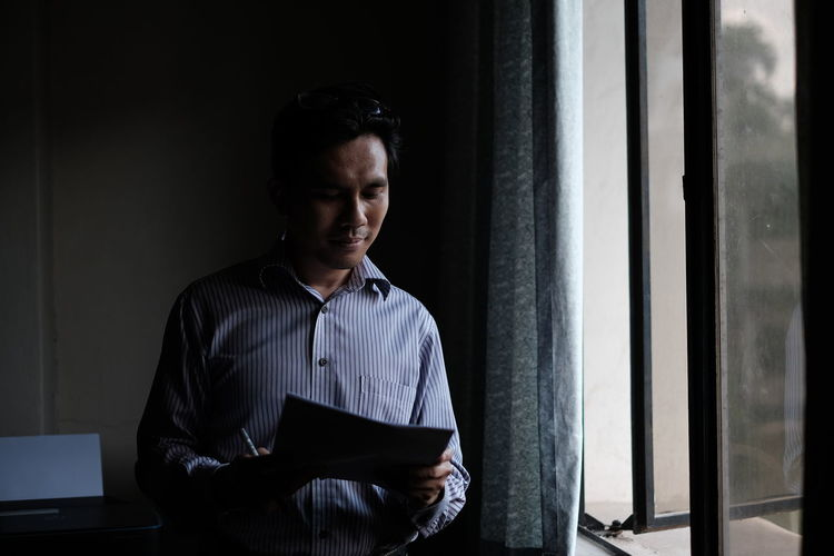 A man read a letter by the windows Business Finance And Industry Businessman Day Front View Indoors  One Man Only One Person People Real People Sitting Standing The Portraitist - 2017 EyeEm Awards Young Adult EyeEmNewHere The Modern Professional