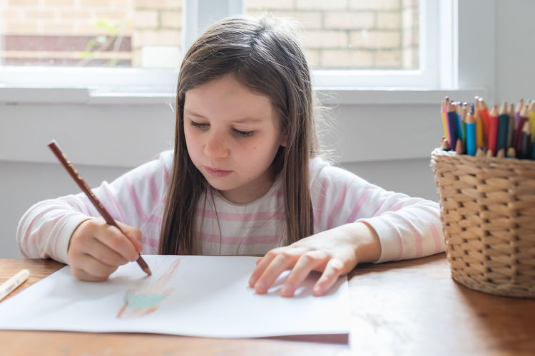 Little girl drawing at the table next to window Child Childhood Table Girls One Person Real People Headshot Females Looking Lifestyles Women Holding Front View Portrait Indoors  Drawing - Activity Concentration Pen Innocence Hairstyle
