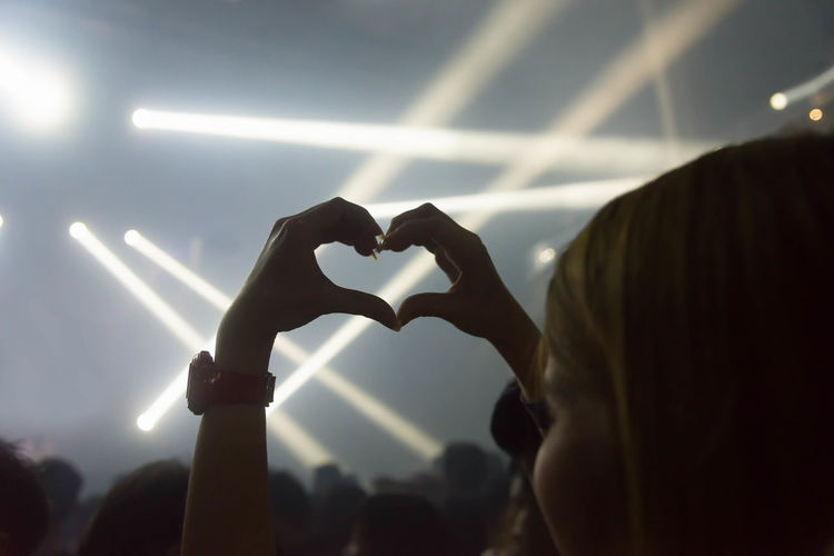 Close-up of person making heat shape at musical concert