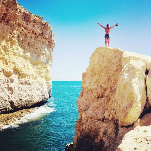 Rock - Object Arms Raised Full Length Sea Rock Formation Arms Outstretched Jumping Sky Day Real People Standing One Person Horizon Over Water Clear Sky Outdoors Men Cliff Scenics Nature Mid-air EyeEmNewHere Nature Open Rocks Sea And Sky Be. Ready. Love Yourself