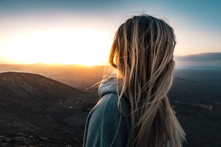 Side view of woman looking at landscape during sunset