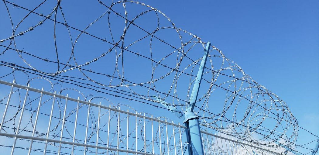 Low angle view of barbed wire against clear sky