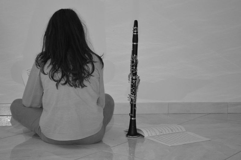 Rear View Of Woman With Clarinet Sitting On Floor