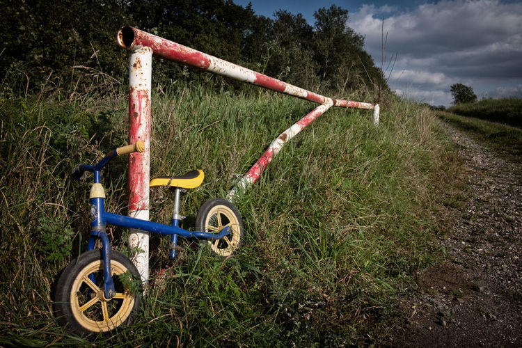 Bicycle parked on field against sky