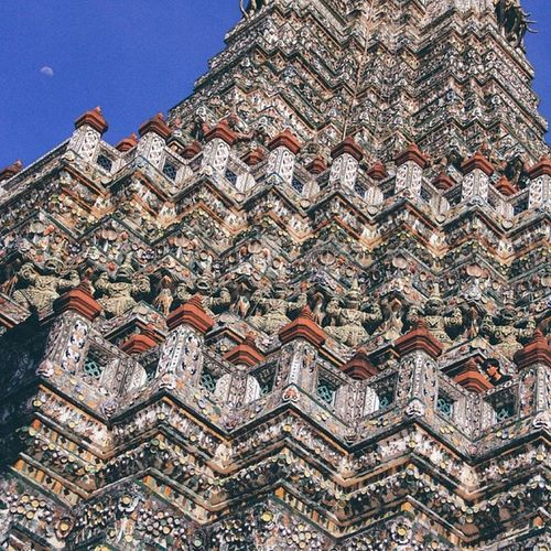 Low Angle View Of Wat Arun Temple Against Blue Sky