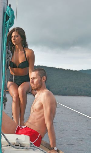 Shirtless Man Sitting With Woman In Boat Against Sky