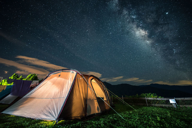 Illuminated tent on land against sky at night