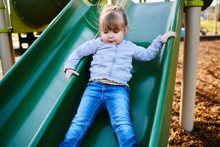 Childhood Child Playground Casual Clothing One Person Slide - Play Equipment Innocence Real People Outdoor Play Equipment Leisure Activity Cute Playing Lifestyles Front View Three Quarter Length Day Outdoors Jungle Gym