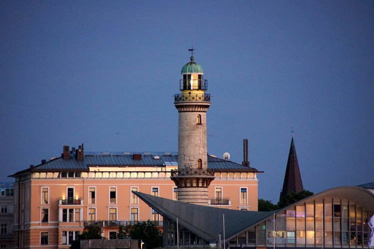 Lighthouse building against sky in city